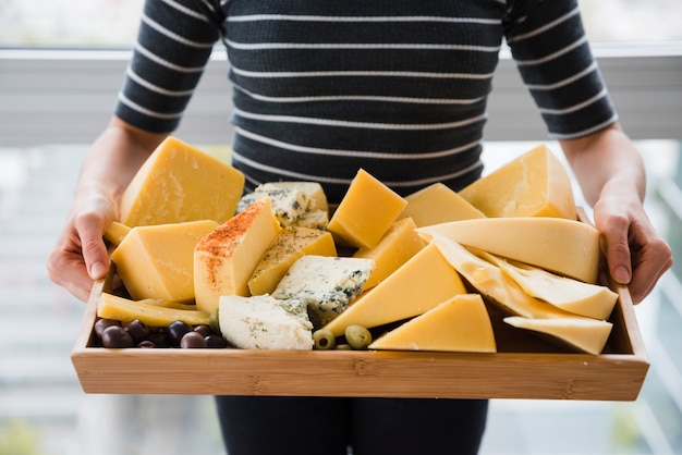 Mid section of woman holding cheese slices in wooden tray Free Photo