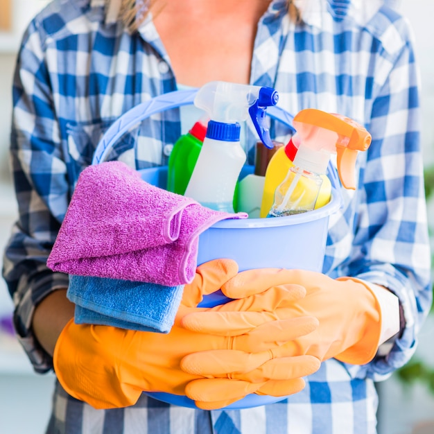 Mid section of woman holding cleaning equipments in the blue bucket Free Photo