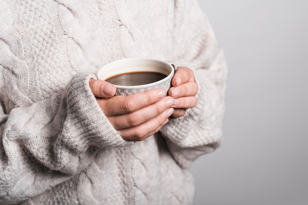 Mid section of woman in woolen clothes holding coffee cup Free Photo