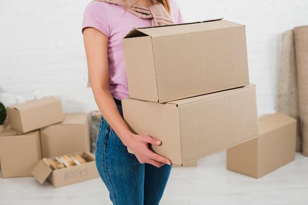 Metà di sezione su una giovane donna che tiene pila di scatole di cartone Foto Gratuite
