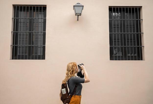 カメラで写真を撮るミッドショア女性 無料写真