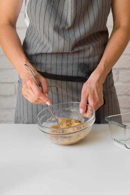 Mid shot baker mashing banana in bowl Free Photo