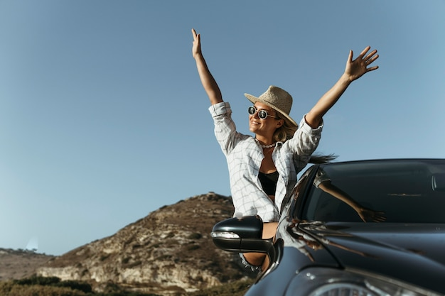 Mid shot blonde woman out of car window with hands in the air Free Photo