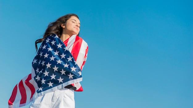 Середине выстрел брюнетка женщина держит большой флаг сша и улыбается Бесплатные Фотографии