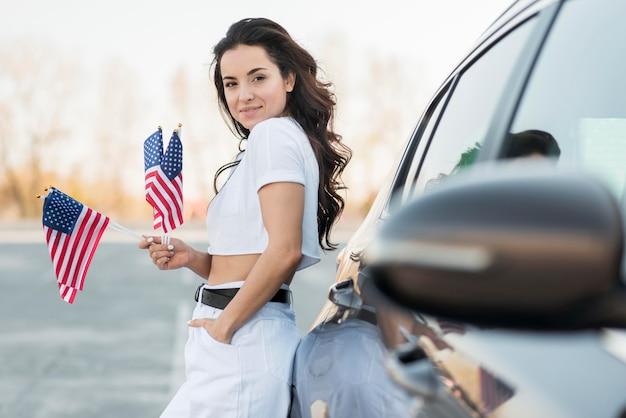 Середине выстрел брюнетка женщина держит флаги сша возле автомобиля Бесплатные Фотографии