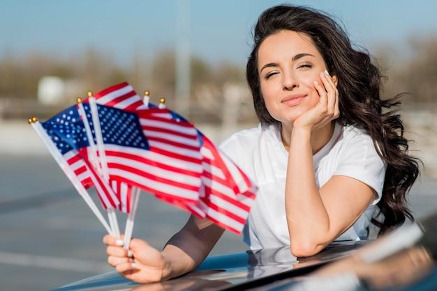 Середине выстрел брюнетка женщина держит флаги сша на машине Бесплатные Фотографии