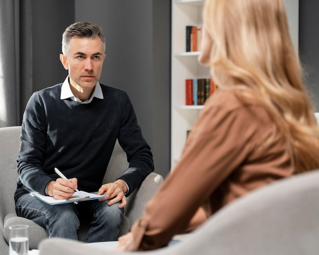 Mid shot counselor with clipboard looking at woman Free Photo