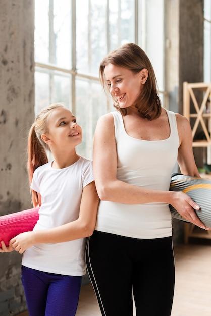 Середина выстрела счастливая мама и девушка держат коврики для йоги Бесплатные Фотографии
