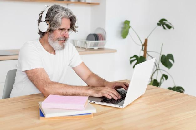 Середине выстрел человек на столе, используя ноутбук Бесплатные Фотографии
