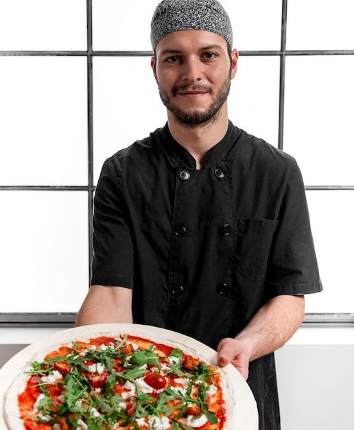 ピザとまな板を保持しているミディアムショットの男 無料写真