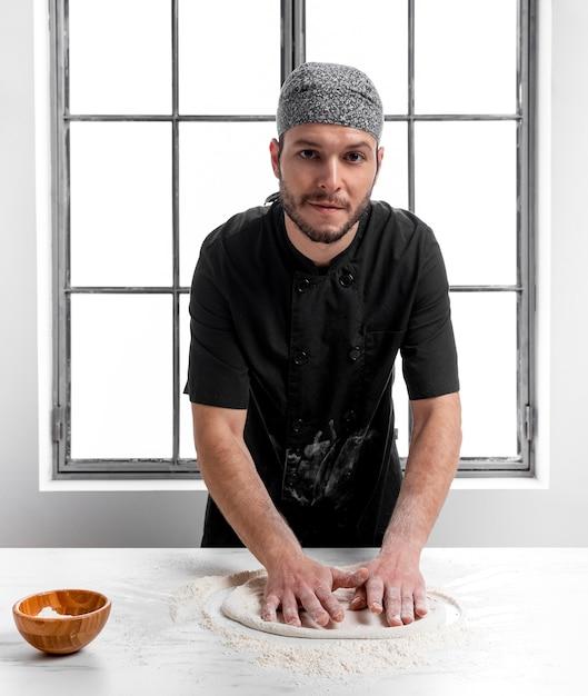 Uomo a metà tiro che fa la pasta della pizza Foto Gratuite