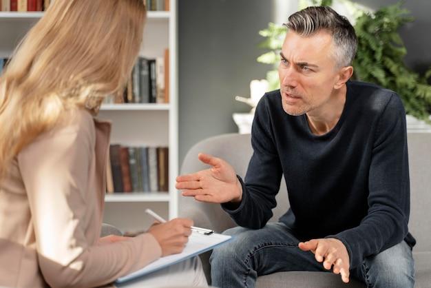 Mid shot man talking to woman therapist Free Photo