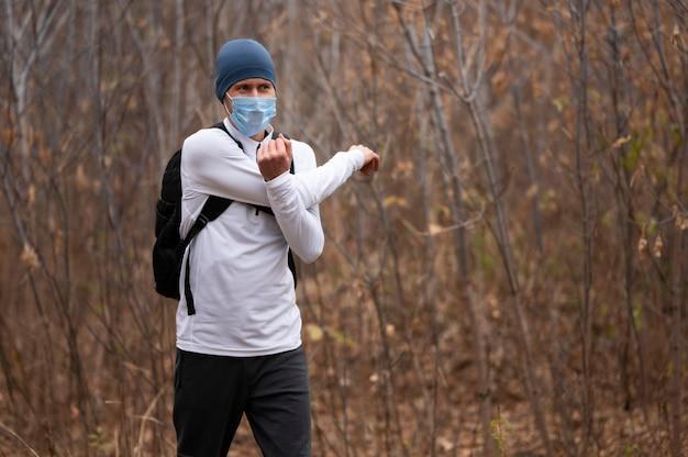 Средний выстрел человека с маской для лица в лесу, протягивая руки Бесплатные Фотографии