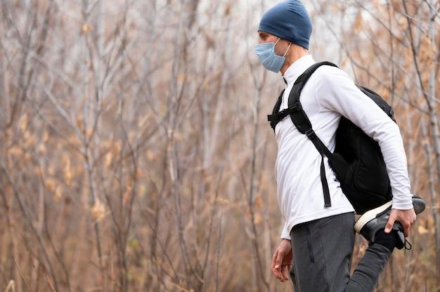Средний выстрел человека с маской для лица в лесу, растягивая ноги Бесплатные Фотографии