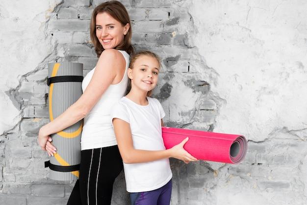 Середина выстрела мама и ребенок держит коврики для йоги Бесплатные Фотографии