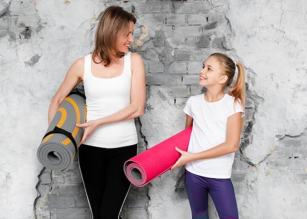 Середина выстрела мама и девушка держат коврики для йоги, глядя друг на друга Бесплатные Фотографии