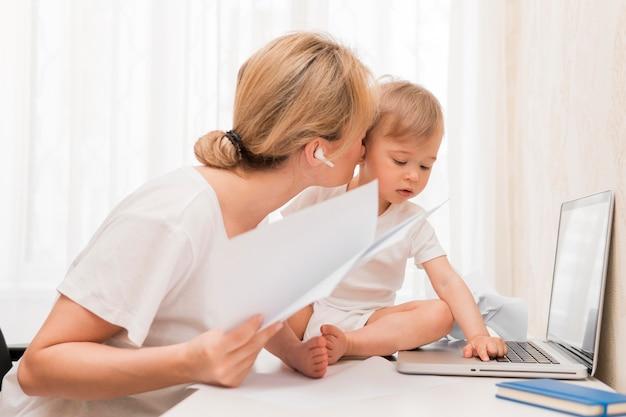 Metà di colpo madre in possesso di documenti e baciare il bambino sulla scrivania Foto Gratuite