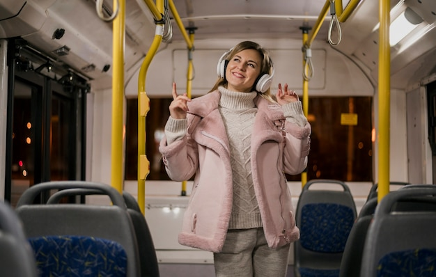 Mid shot smiling woman wearing headphones in bus Free Photo