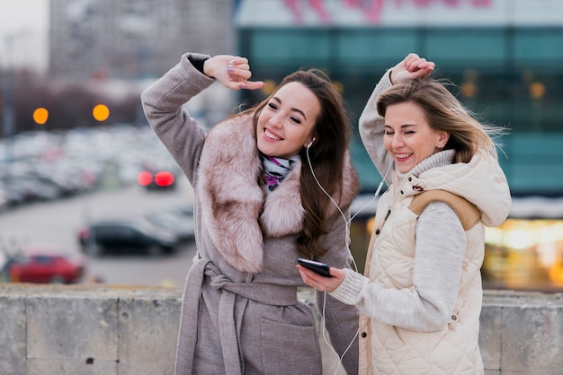 Mid shot smiling women with earphones on roof Free Photo