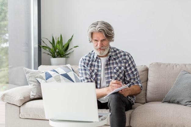 Insegnante del mezzo colpo che esamina computer portatile e che annota Foto Gratuite