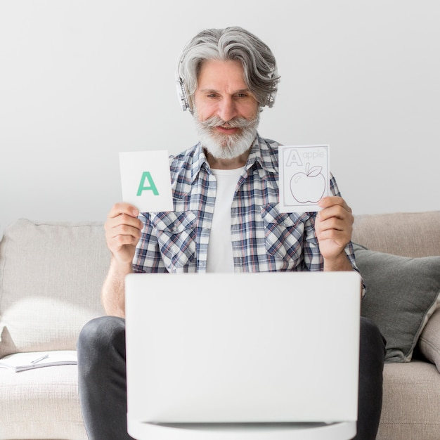 Mid shot teacher showing flash cards at laptop Premium Photo