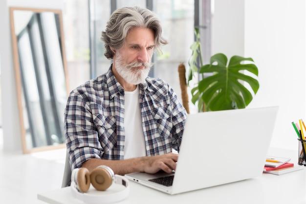 Insegnante del mezzo colpo che resta allo scrittorio facendo uso del computer portatile Foto Gratuite