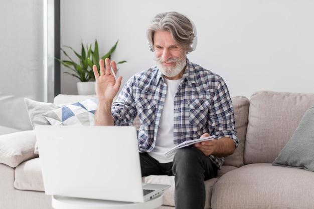 Середина выстрел учитель машет рукой на ноутбуке Premium Фотографии