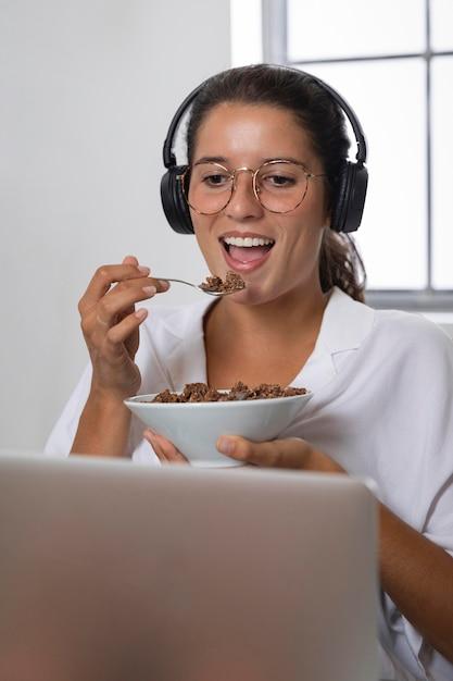 Donna del colpo metà che mangia davanti al computer portatile Foto Gratuite