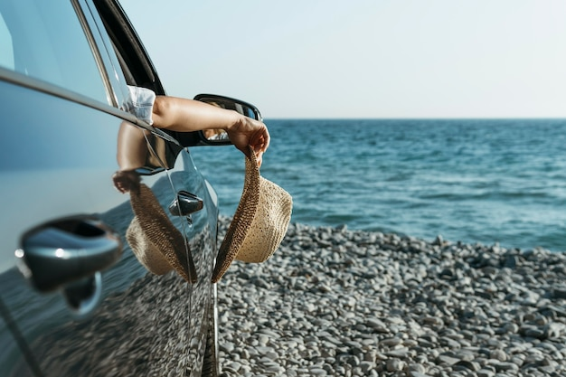 Mid shot woman handhanging out of car windowand holding hat near sea Free Photo