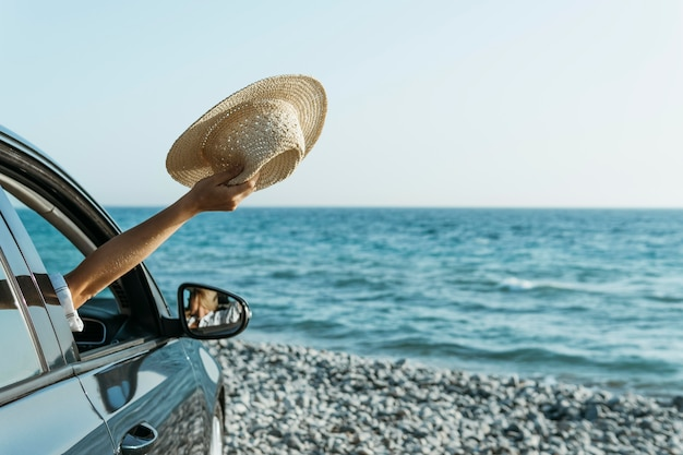 Mid shot woman hand out of car window and holding hat near sea Free Photo