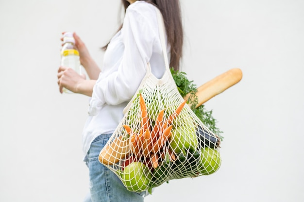 Mid shot woman holding reusable with groceries bag outside Premium Photo
