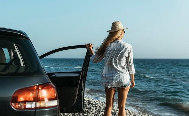 Mid shot woman looking at sea by car Free Photo