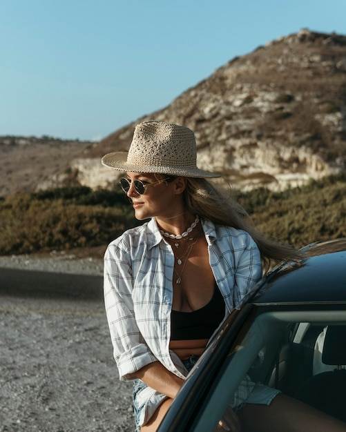 Mid shot woman standing out of car window on beach Free Photo