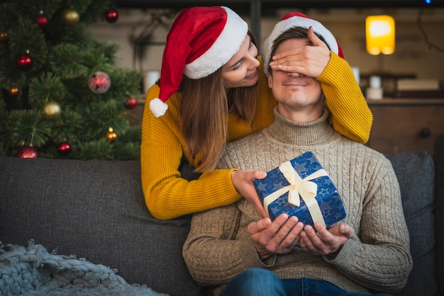 Mid shot woman surprising man with gift Free Photo