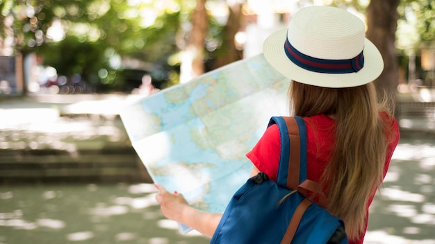 Mid shot woman with hat and map outside Premium Photo