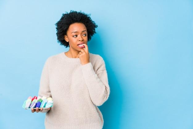 マカロンを食べる中年のアフリカ系アメリカ人女性は、コピースペースを見て何かについてリラックスした思考を分離しました。 Premium写真