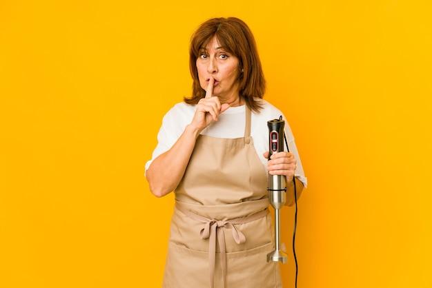 ミキサーを持っている中年の白人料理人の女性は、秘密を守るか、沈黙を求めて孤立しました。 Premium写真