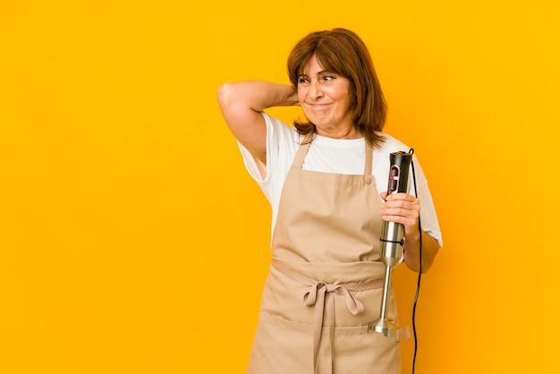 頭の後ろに触れて、考えて、選択をすることを分離したミキサーを持っている中年の白人料理人の女性。 Premium写真