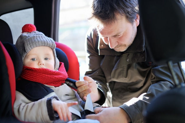 Middle age father helps his toddler son to fasten belt on car seat Premium Photo