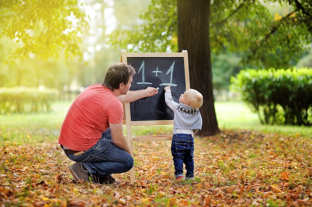 Middle age father and his toddler son at blackboard practicing mathematics Premium Photo