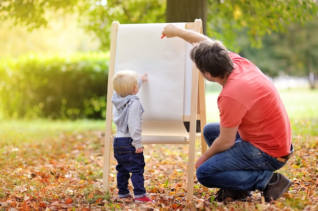 Middle age father and his toddler son drawing on white empty paper Premium Photo