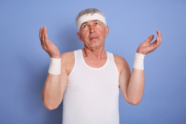 Middle age handsome sportsman, looks clueless and confused, keep arms raised, has no idea, wearing white sleeveless t-shirt and hear band, standing isolated. Free Photo
