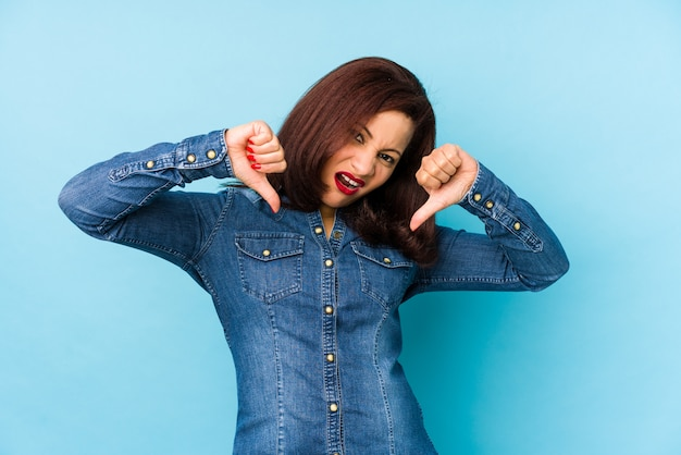 Middle age latin woman isolated on blue showing thumb down and expressing dislike. Premium Photo