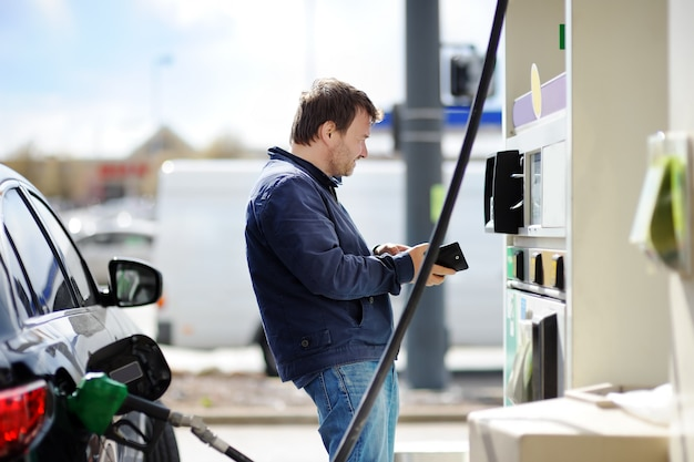 Middle age man filling gasoline fuel in car Premium Photo