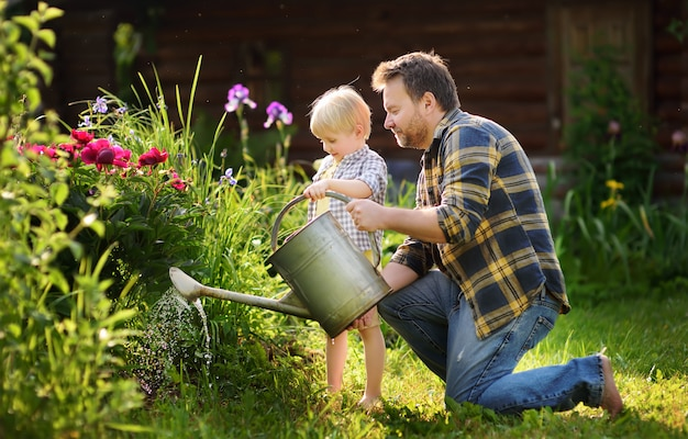 Middle age man and his little son watering flowers in the garden at summer sunny day Premium Photo
