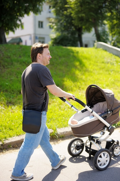 Middle age man walking with baby stroller Premium Photo