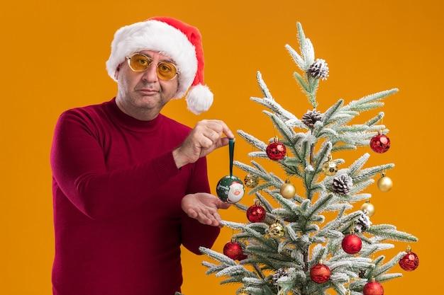 Uomo di mezza età che indossa il cappello di babbo natale in dolcevita rosso scuro e occhiali gialli con un sorriso scettico che decora l'albero di natale Foto Gratuite