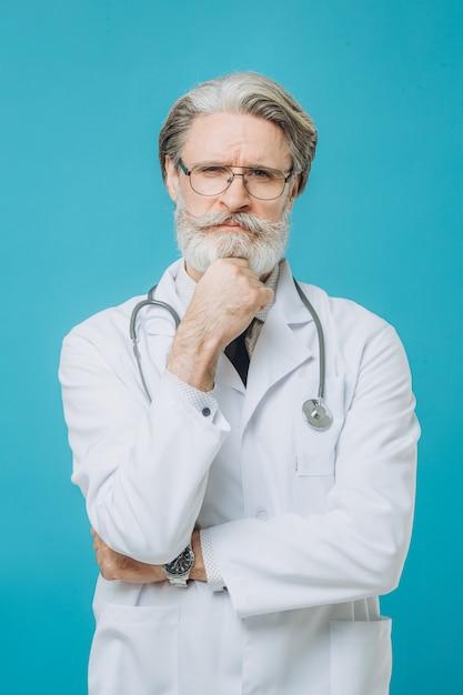 Человек доктора среднего возраста старший седой доктор нося медицинскую форму изолировал стену с серьезным выражением на стороне. Premium Фотографии