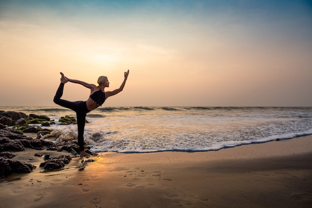 Middle age woman in black doing yoga on sand beach in india natarajasana pose Premium Photo