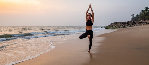 Middle age woman in black doing yoga on sand beach in india at sunset Premium Photo